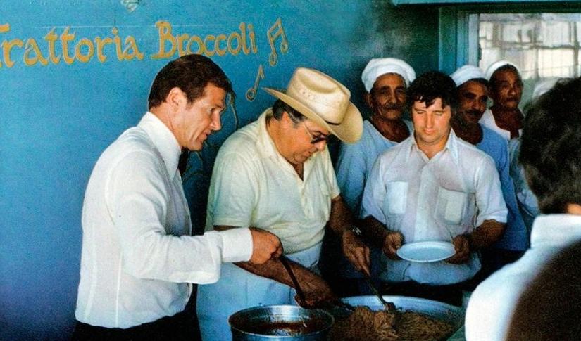 Roger Moore e Cubby servem almoço para a equipe © 1977 Danjaq LLC, United Artist Corporation. Todos os Direitos Reservados.